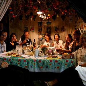 Pic: Bridges for Peace volunteers (from Canada, the United Kingdom, the U.S., South Africa, and Japan) celebrate the Feast of the Tabernacles in a traditional sukkah (booth) with local Israelis.  Photo courtesy Bridges for Peace Canada