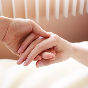 Holding hand of a sick loved one
